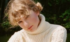 Taylor Swift wearing a cream roll neck jumper with soft curls (mid shot)